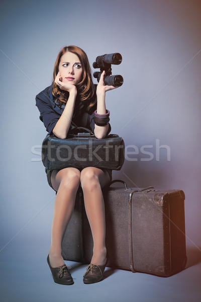 photo of beautiful young woman sitting on suitcase and holding b Stock photo © Massonforstock