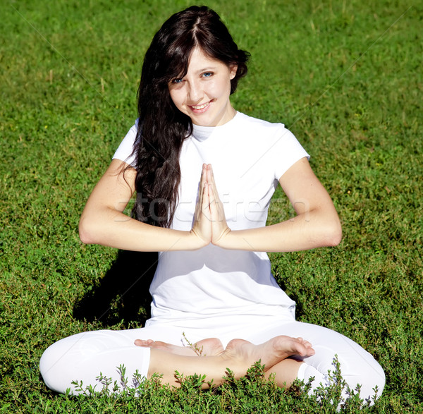 Beautiful young brunet yoga girl on green grass in park. Stock photo © Massonforstock