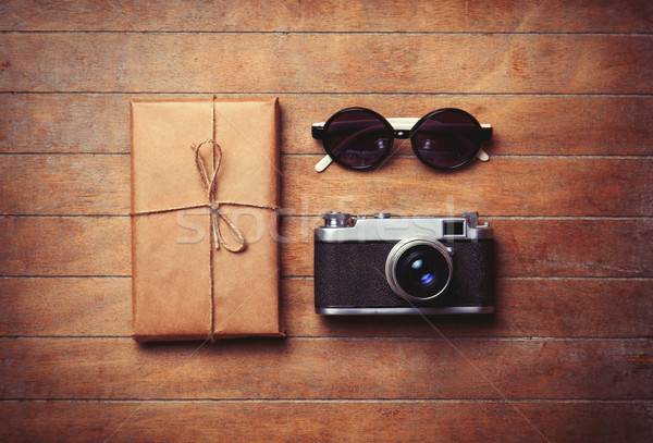 Vintage camera and sunglasses with package on wooden table. Photo in old color image style. Stock photo © Massonforstock