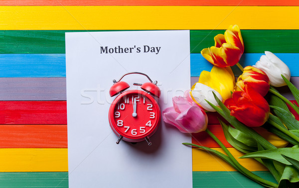 bunch of tulips, red clock ans sheet of the paper lying on the t Stock photo © Massonforstock