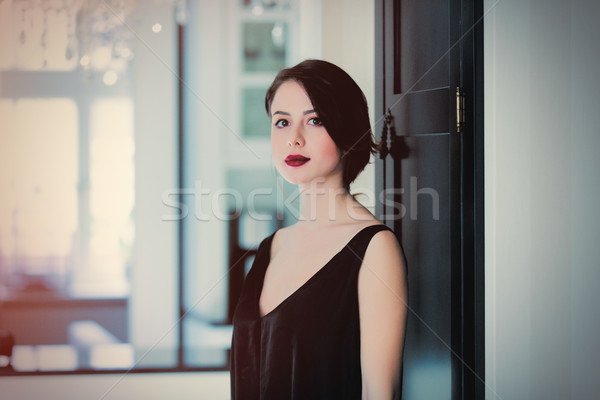 beautiful young woman standing near the door in the light luxury Stock photo © Massonforstock