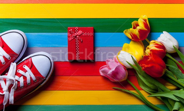 bunch of tulips, red gumshoes and gift lying on the table Stock photo © Massonforstock