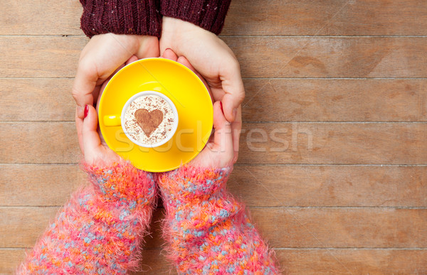 Stock photo: photo of male and female hands holding cup of coffee on the wond