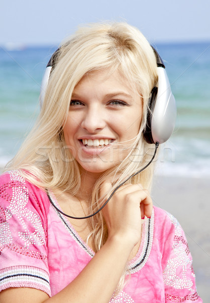 Young blonde girl with headphone on the beach. Stock photo © Massonforstock