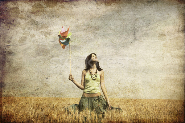 Girl with wind turbine at wheat field. Photo in old color image  Stock photo © Massonforstock