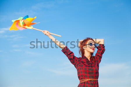 Redhead girl with colour balloons at blue sky background.  Stock photo © Massonforstock