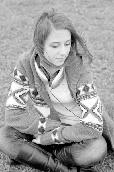 Sad girl with headphones sitting at grass. Photo in black and wh Stock photo © Massonforstock