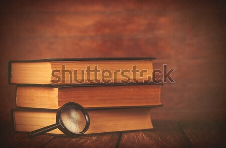 Books with loupe on wooden background. Stock photo © Massonforstock