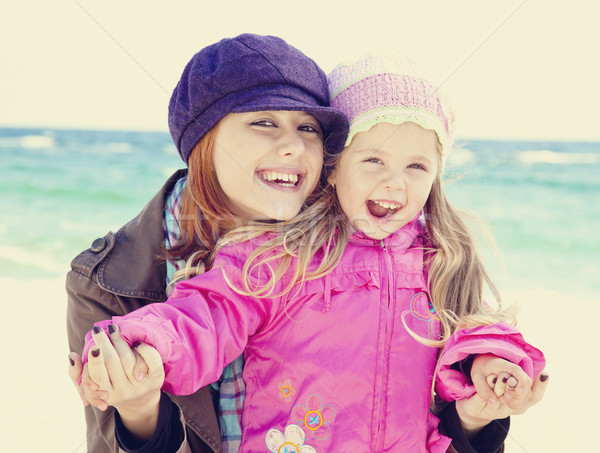 Two sisters 4 and 21 years old at the beach in sunny autumn day. Stock photo © Massonforstock