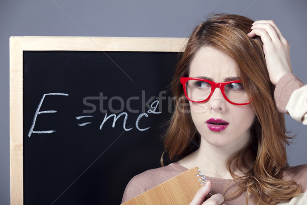 Surprised redhead student near blackboard.  Stock photo © Massonforstock