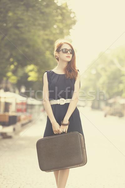 Stock photo: Young woman with suitcase on the city street