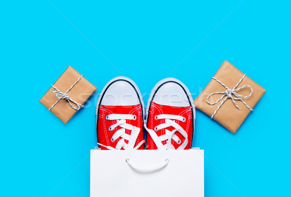 big red gumshoes in cool shopping bag and beautiful gifts on the Stock photo © Massonforstock