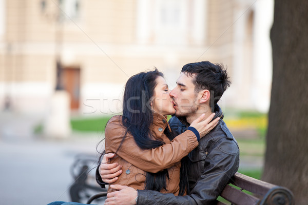 photo of cute couple sitting on the bench and kissing on the won Stock photo © Massonforstock