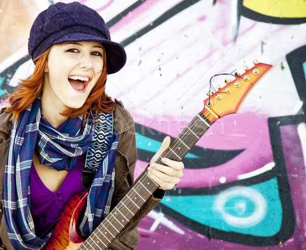Closeup portrait of a happy young girl with guitar and graffiti  Stock photo © Massonforstock