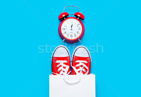 big red gumshoes in cool shopping bag and alarm clock on the won Stock photo © Massonforstock