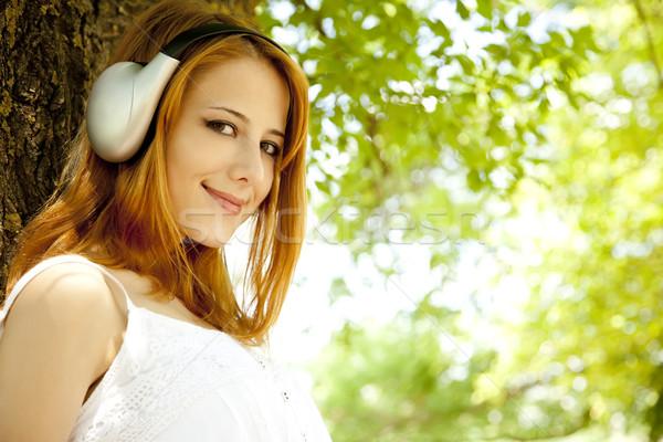Gyönyörű vörös hajú nő lány fejhallgató kert nők Stock fotó © Massonforstock