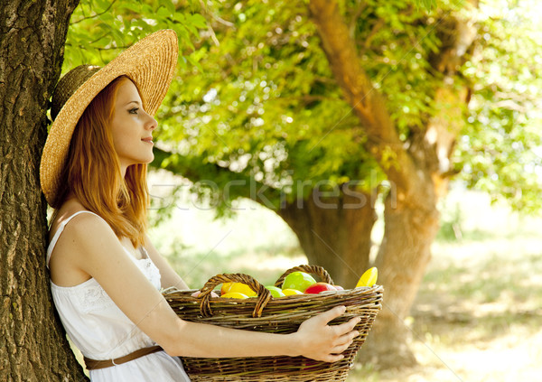 Beautiful redhead girl with fruits in basket at garden. Stock photo © Massonforstock