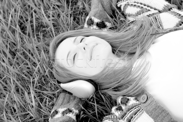 Young fashion girl with headphones lying at grass. Photo in blac Stock photo © Massonforstock