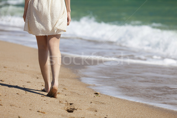 Cropped image of a young woman walking on a beach Stock photo © Massonforstock