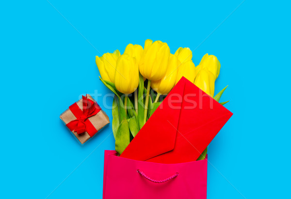 bunch of yellow tulips and red envelope in cool shopping bag and Stock photo © Massonforstock