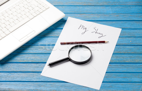 photo of paper My story, magnifying glass and laptop on the wond Stock photo © Massonforstock