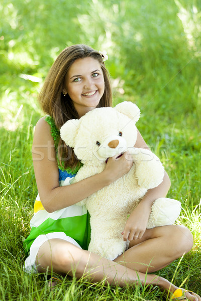 Beautiful teen girl with Teddy bear in the park at green grass. Stock photo © Massonforstock