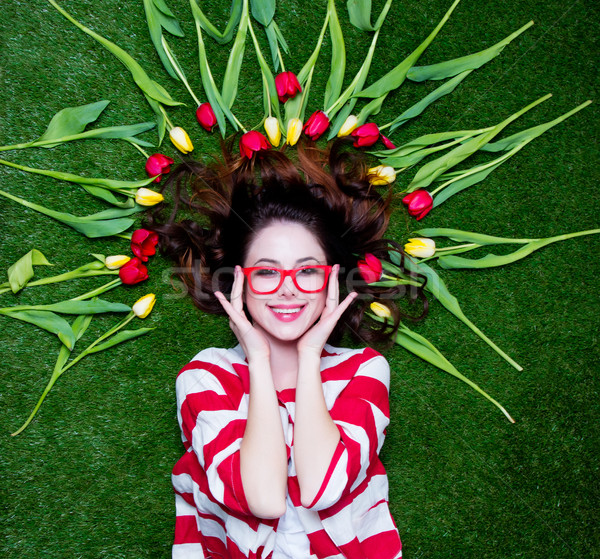 Portrait of a young styled redhead woman tulips around and glass Stock photo © Massonforstock
