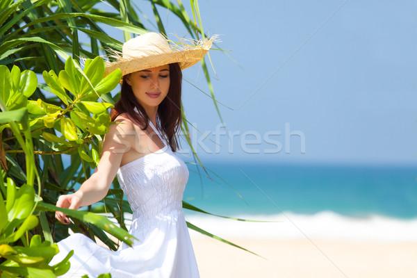Gyönyörű fiatal nő áll egzotikus fa mosolyog Stock fotó © Massonforstock