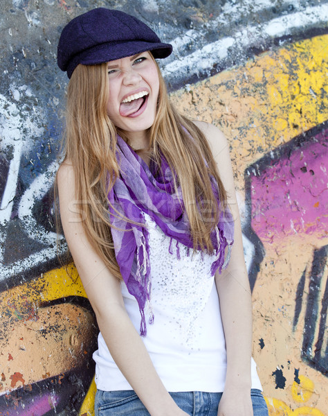 Grimacing teen girl near graffiti wall. Stock photo © Massonforstock