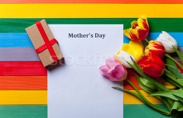 bunch of tulips, gift and sheet of the paper lying on the table Stock photo © Massonforstock