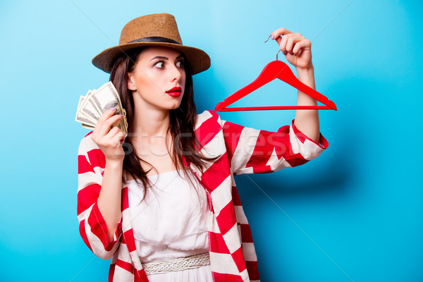 beautiful young woman with hanger and money standing in front of Stock photo © Massonforstock