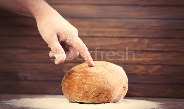 male hand touching bread loaf on the wonderful brown wooden back Stock photo © Massonforstock