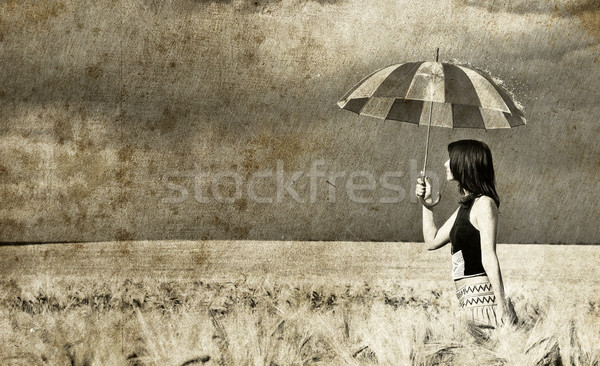 Stock photo: Girl with umbrella at field. Photo in old retro style.