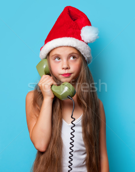girl in Santas hat calling by phone Stock photo © Massonforstock