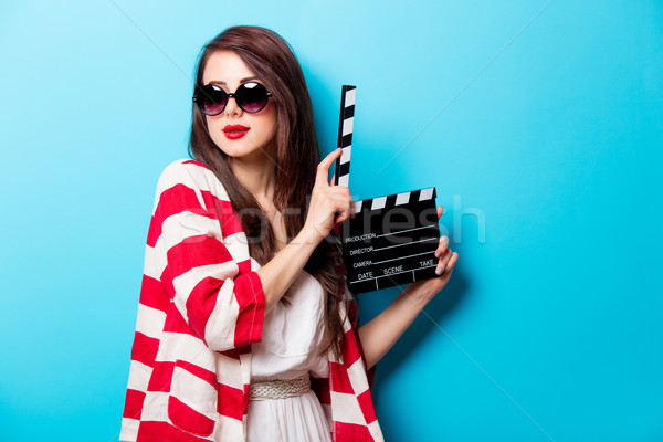 beautiful young woman with cinema clapper standing in front of w Stock photo © Massonforstock