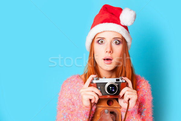 Redhead girl in hat and camera on yellow background. Stock photo © Massonforstock