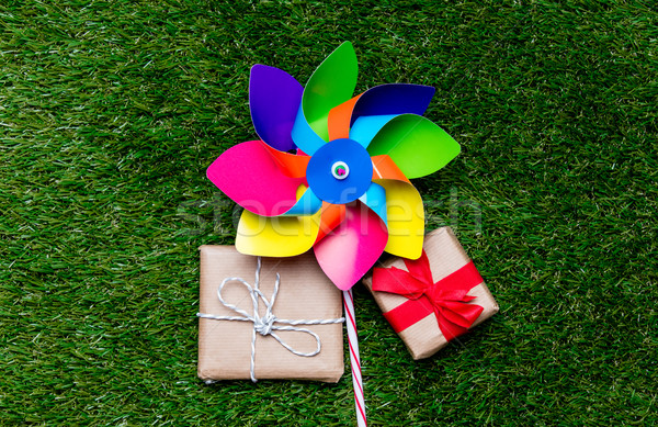 pinwheel toy and two gift boxes on green grass background, above Stock photo © Massonforstock