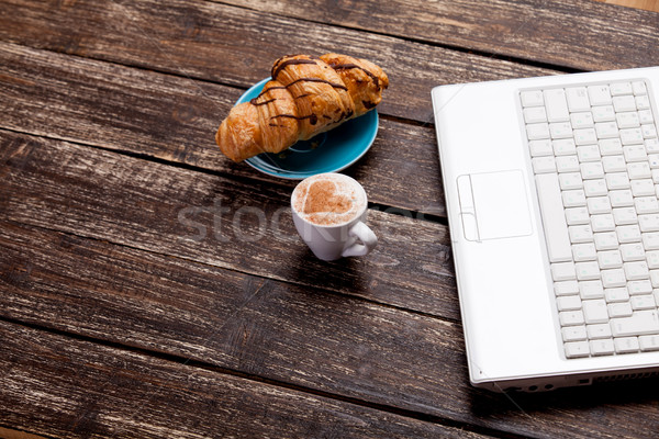 photo of delicious fresh croissant, laptop and cup of coffee on  Stock photo © Massonforstock