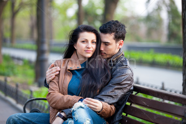 photo of cute couple sitting on the bench and hugging on the won Stock photo © Massonforstock