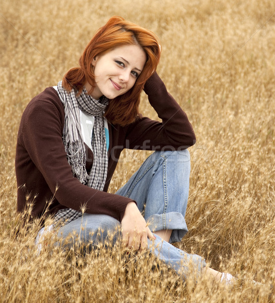 Beautiful red-haired girl at yellow autumn grass. Stock photo © Massonforstock