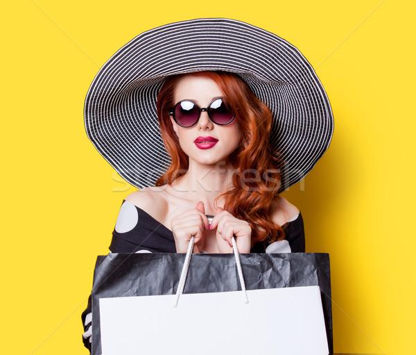 Lány fekete ruha kalap bevásárlótáskák vörös hajú nő citromsárga Stock fotó © Massonforstock