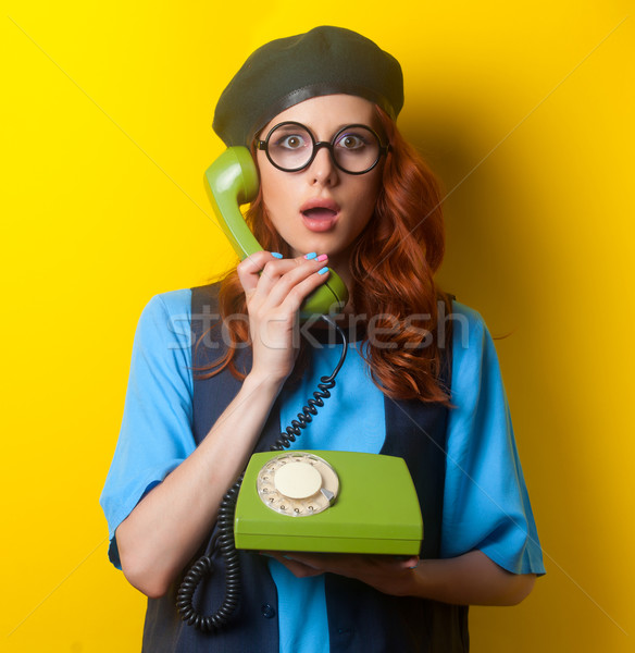 Surprised redhead girl with dial phone  Stock photo © Massonforstock