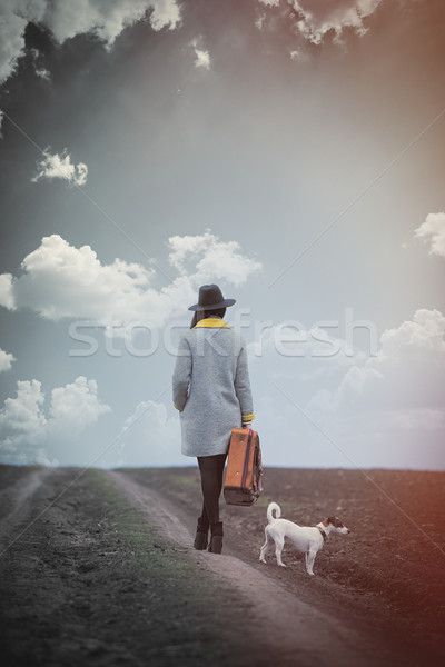 beautiful young woman standing with suitcase near dog on the won Stock photo © Massonforstock