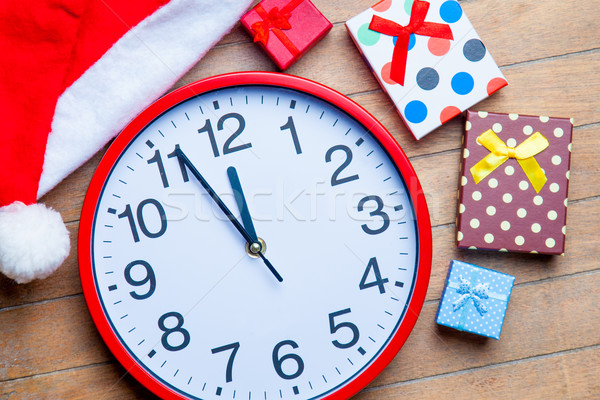 gifts, clock and santa claus hat on the wonderful brown wooden b Stock photo © Massonforstock