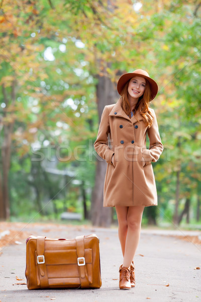 photo of beautiful young woman standing near suitcase on the won Stock photo © Massonforstock