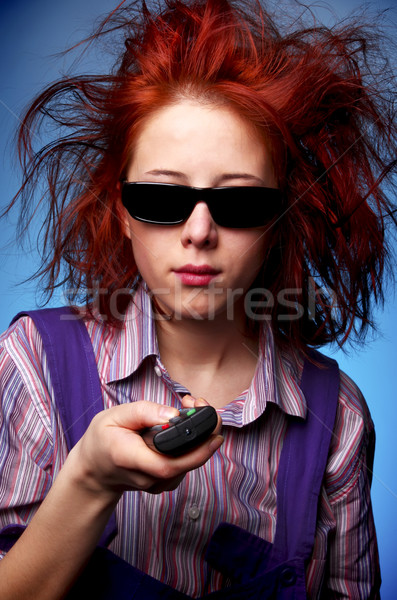 Funny red-haired girl in glasses with TV remote Stock photo © Massonforstock