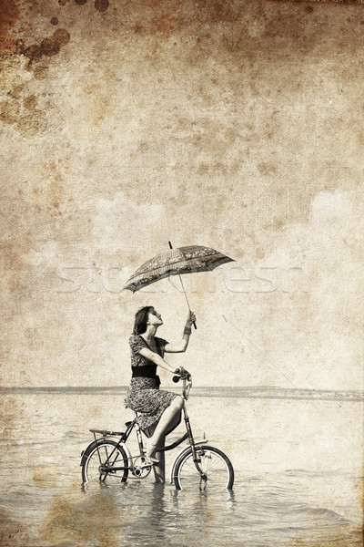 Girl with umbrella on bike. Photo in old image style.  Stock photo © Massonforstock