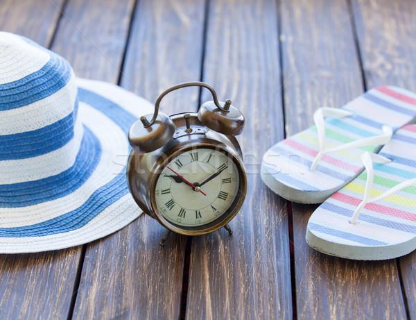 Alarm clock and hat with flip flops  Stock photo © Massonforstock