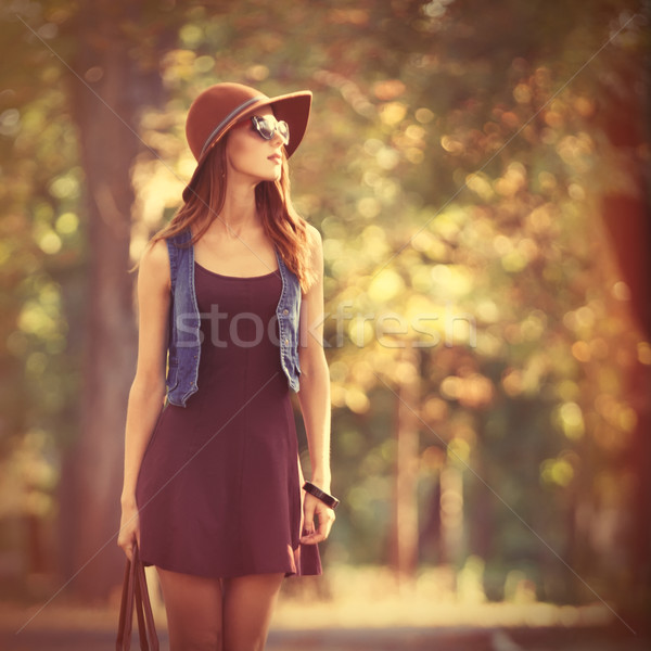 Beautiful redhead girl with bag in the park. Stock photo © Massonforstock