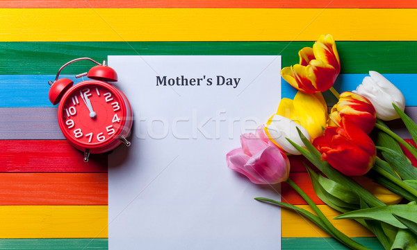 sheet of the paper, red clock and bunch of tulips lying on the t Stock photo © Massonforstock